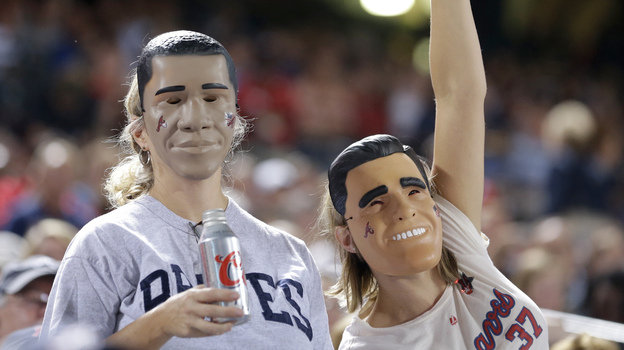 Fans wear President Obama and Mitt Romney masks at the Atlanta Braves-Miami Marlins game Sept. 25 in Atlanta. One of many quirky election year predictors is based on which candidate's likeness sells better as a Halloween mask. (AP)