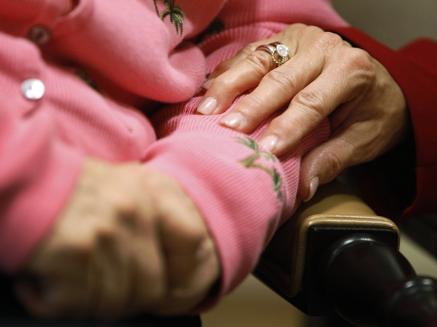 Alexis McKenzie, executive director of the Methodist Home of the District of Columbia Forest Side, an Alzheimer's assisted-living facility, puts her hand on the arm of resident Catherine Peake. (AP)