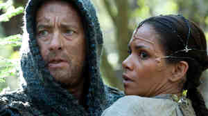 Zachry and Meronym are only two of the combined 12 characters Tom Hanks and Halle Berry play in Cloud Atlas. It is a challenge that bests both actors, according to David Edelstein.