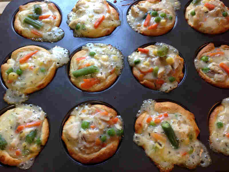 Bubbling chicken potpie cupcakes, fresh out of the oven. Crescent roll dough creates a shell for the chicken filling.