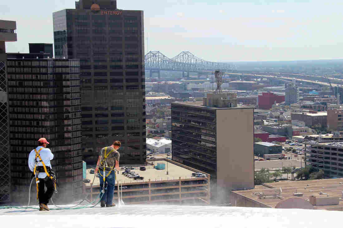 """Rene Lopez and Devin Burrell blast dirt off the polyurethane coating the iconic white roof of the Superdome in New Orleans. The job will cost about $130,000 and take roughly a month, partly because the roofers must move slowly. """"You have to constantly be aware of where you're at,"""" says project manager Tom Keller. """"If something stupid happens, it's not going to end up pretty."""""""
