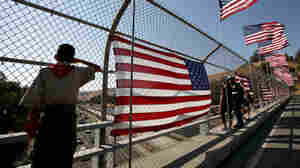 A Boy Scout salutes traffic as he stands next to a flag display on a freeway overpass September 11, 2008 in Lafayette, California.
