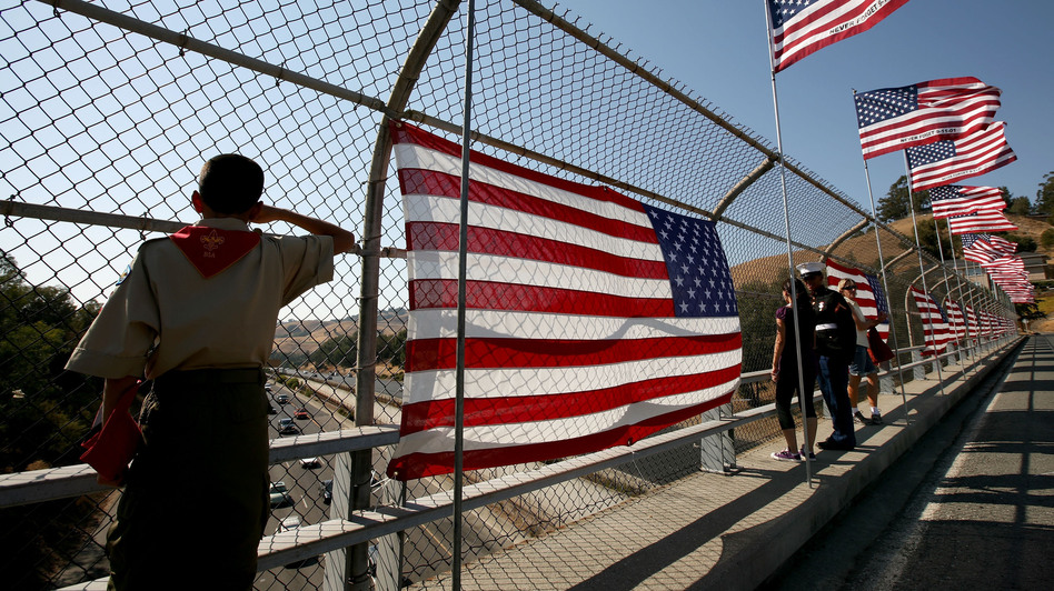 A Boy Scout salutes traffic as he stands next to a flag display on a freeway overpass September 11, 2008 in Lafayette, California. (Getty Images)