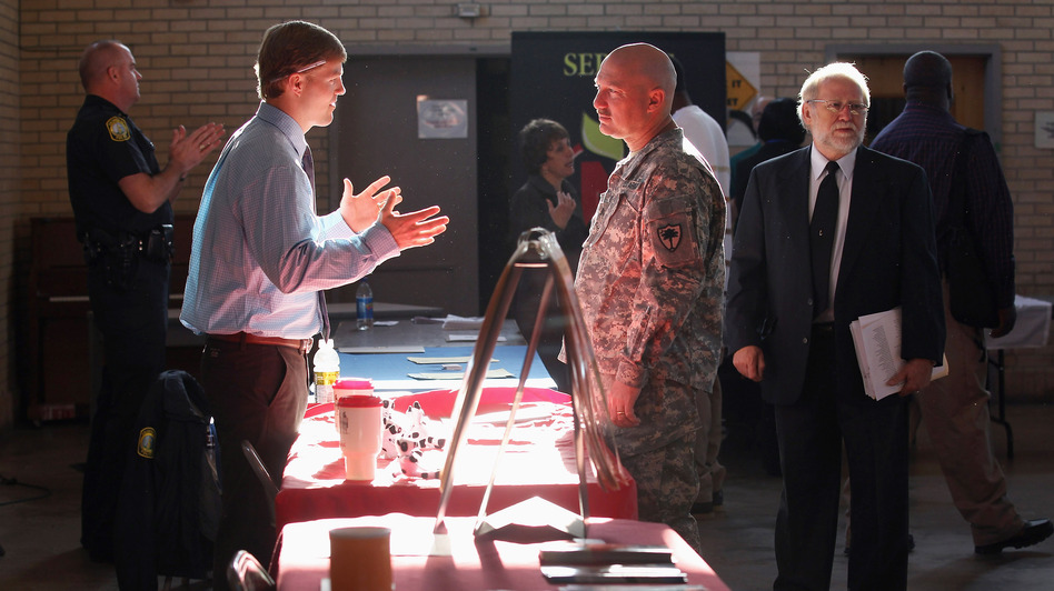 Sgt. Ben Roberts (center), recently returned from Afghanistan, speaks with Chick-fil-A manager Michael Sims at a military job fair in Columbia, S.C., in January. (Getty Images)
