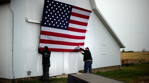 Aides tack up an American flag to a barn at the James Koch farm in Van Meter, Iowa, on Oct. 9, ahead of Republican presidential candidate Mitt Romney's arrival for a rally.