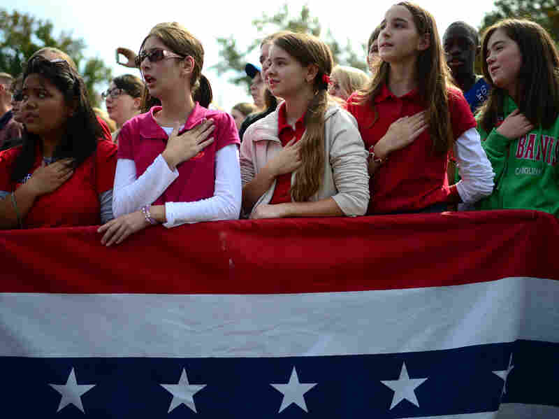 The crowd joins Republican Mitt Romney in singing the national anthem at a rally Wednesday in Chesapeake, Va.
