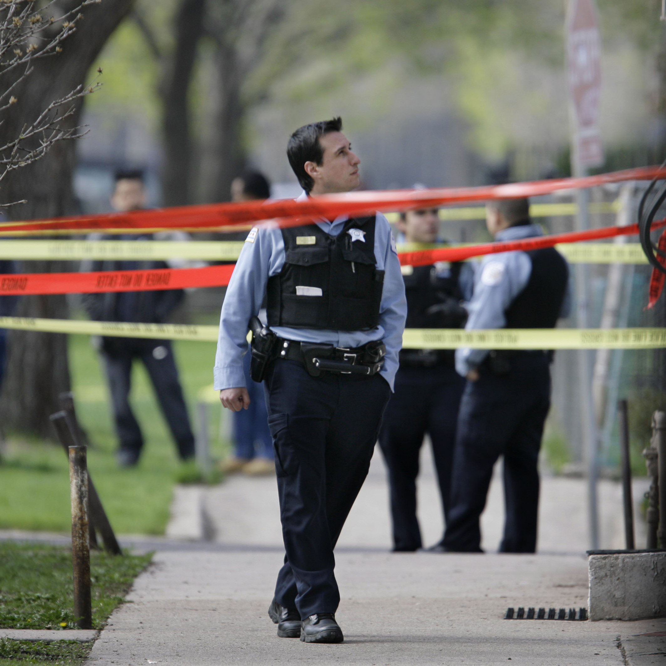 Police officers work a crime scene where they discovered the bodies of three shooting victims at a home on Chicago's Southwest side in April 2008. The number of shootings and homicides in the city is increasing, but many of these crimes are going unsolved.