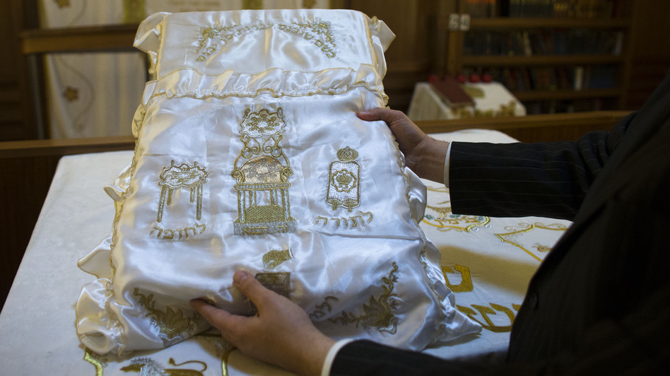 A rabbi holds up a pillow used during ritual circumcision at a synagogue in Berlin.