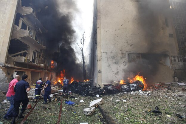 Lebanese firefighters extinguish burning cars in Beirut following a huge bomb explosion.