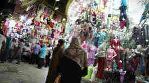 Nighttime shoppers pause to look at a display at Cairo's Ataba market in May 2011. The government says shops must close earlier in order to save scarce electricity, but many Cairo residents are complaining.