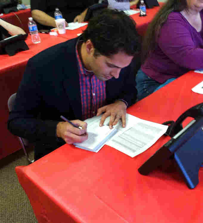 Craig Romney, the son of Republican presidential candidate Mitt Romney, signs postcards to voters at a campaign office in Aurora, Colo.