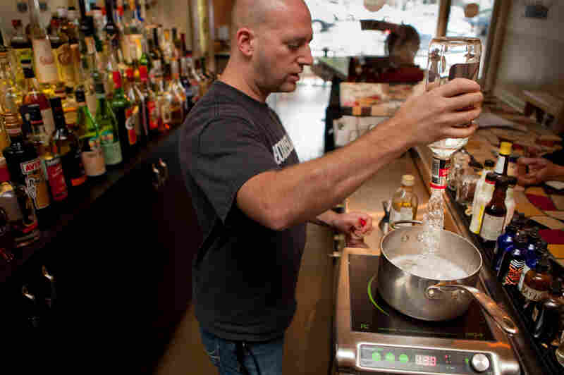 Josh Berner of Ripple, a bar and restaurant in Washington, D.C., pours a bottle of gin into a pot over a very low heat.