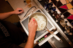 Berner stirs the oil into the simmering gin and cooks and stirs for about 20 minutes.