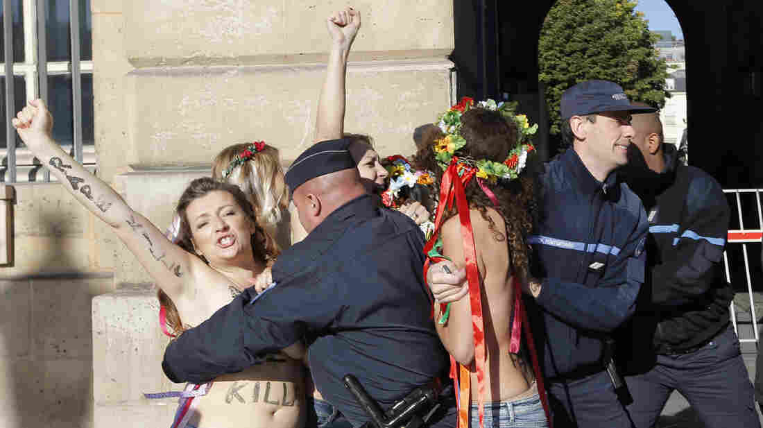 French policemen on Oct. 15 detain topless activists from the group Femen who are protesting the verdict in a gang rape trial. The group was established in Ukraine but is now setting up an office in Paris.