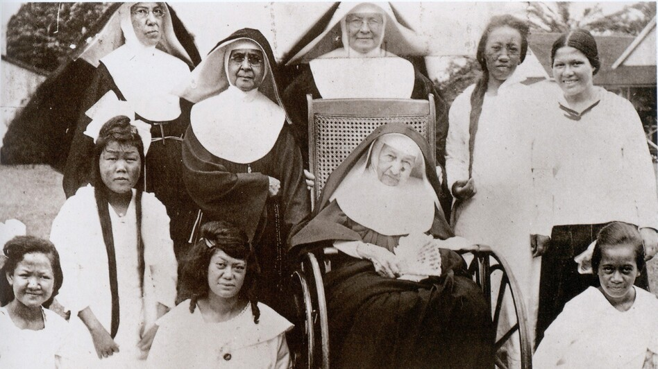 Mother Marianne Cope (in wheelchair) with other nuns and the women and girls of Bishop Home in Kalaupapa, Hawaii, shortly before her death in 1918. (Sisters of St. Francis Archive)