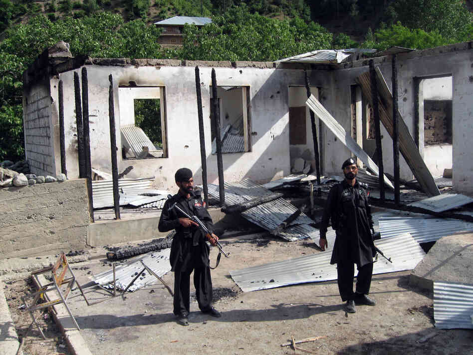 Pakistani security personnel stand guard in front of a burnt-out school following an attack by the Pakistani Taliban in the northwestern district of Upper Dir in June 2011. The Taliban have destroyed many schools in northwestern Pakistan.