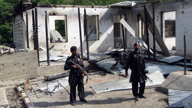 Pakistani security personnel stand guard in front of a burnt-out school following an attack by the Pakistani Taliban in the northwestern district of Upper Dir in June 2011. The Taliban have destroyed many schools in northwestern Pakistan. (Getty Images)