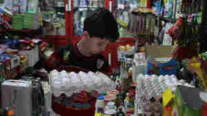 An Iranian boy holds a tray of eggs at a grocery store in Tehran last month. From Sunday, Sept. 30, to Monday, Oct. 1, the Iranian currency lost nearly one-third of its value against the dollar.