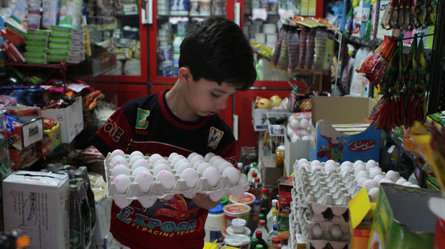 An Iranian boy holds a tray of eggs at a grocery store in Tehran last month. From Sunday, Sept. 30, to Monday, Oct. 1, the Iranian currency lost nearly one-third of its value against the dollar. (AFP/Getty Images)
