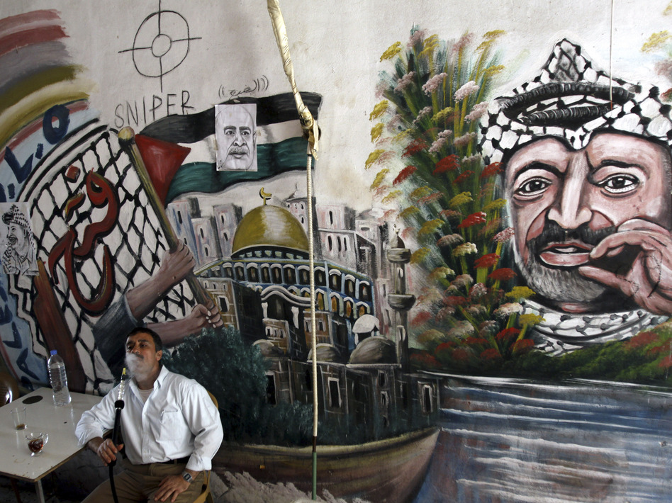 A Palestinian man smokes a nargileh (waterpipe) next to a mural of the late Palestinian leader Yasser Arafat in a coffee shop in the West Bank city of Jenin in September. (AP)