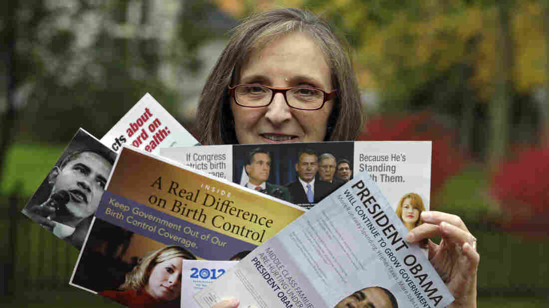 Jean Gianfagna displays some of the political mailings her family receives at her home in Westlake, Ohio, on Oct. 19. Gianfagna says her family sometimes gets four of the same piece at a time — her husb