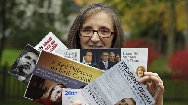 Jean Gianfagna displays some of the political mailings her family receives at her home in Westlake, Ohio, on Oct. 19. Gianfagna says her family sometimes gets four of the same piece at a time — her husband and two grown kids all get their own.