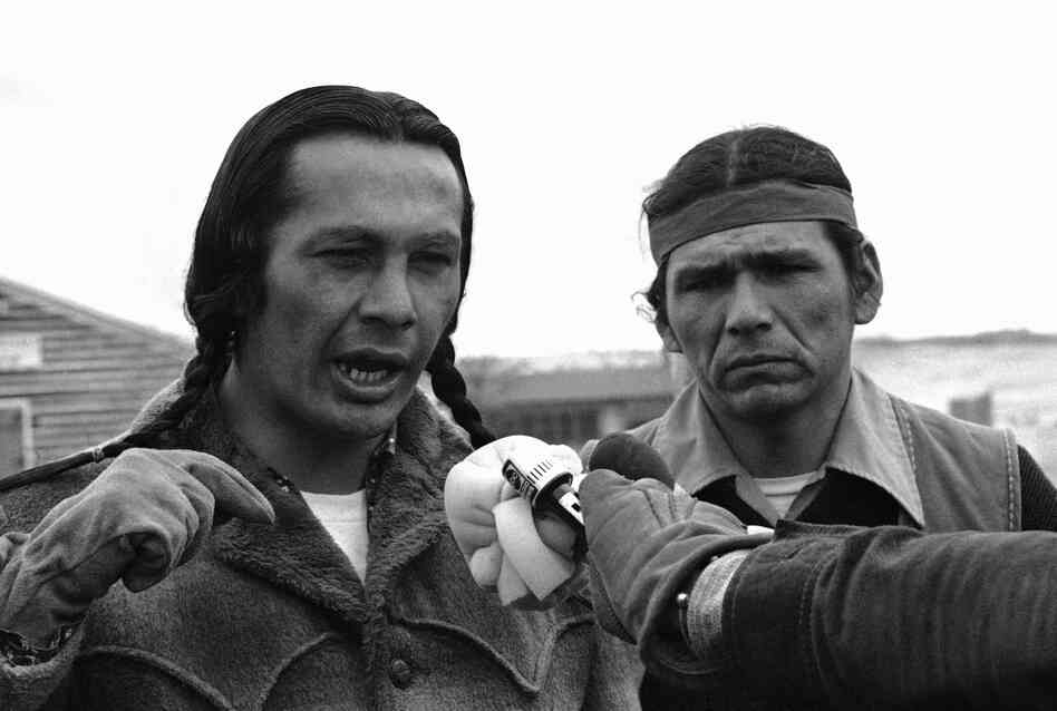 Russell Means, left, talks to media in 1973 in the village of Wounded Knee, South Dakota.