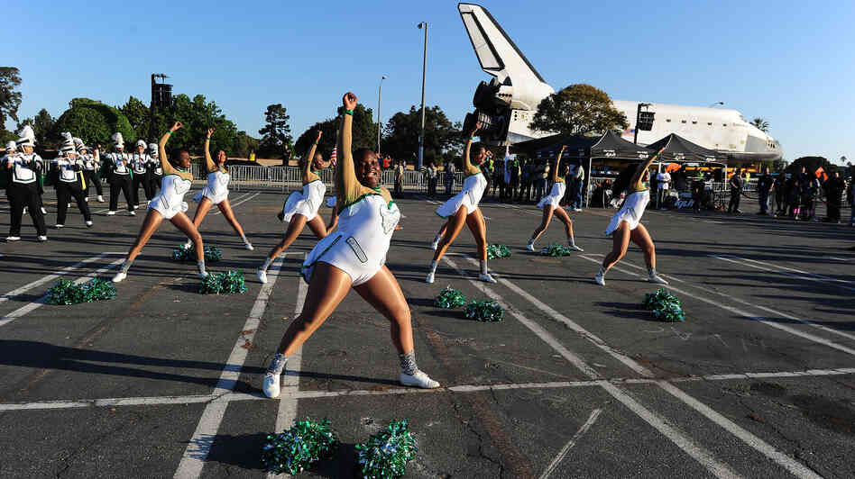 Inglewood High School cheerleaders perform in front of the Space Shuttle Endeavour as it is transported through the streets of Inglewood and Los Angeles on October 13.