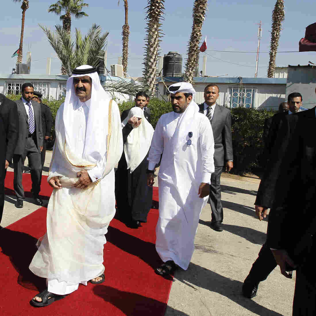 Qatari Emir Sheikh Hamad bin Khalifa al-Thani (center right) walks alongside Gaza's Hamas prime minister Ismail Haniya (center left) during a welcome ceremony at the Rafah border crossing with Egypt on Tuesday.