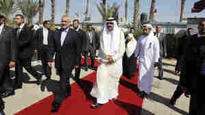 Qatari Emir Sheikh Hamad bin Khalifa al-Thani (center right) walks alongside Gaza's Hamas prime minister Ismail Haniya (center left) during a welcome ceremony at the Rafah border crossing with Egypt on Tuesday.