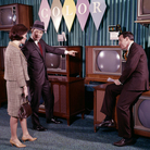 A couple talks to a salesman about buying a color TV set. Over the years, televisions have evolved to include color, high-definition and 3-D models.