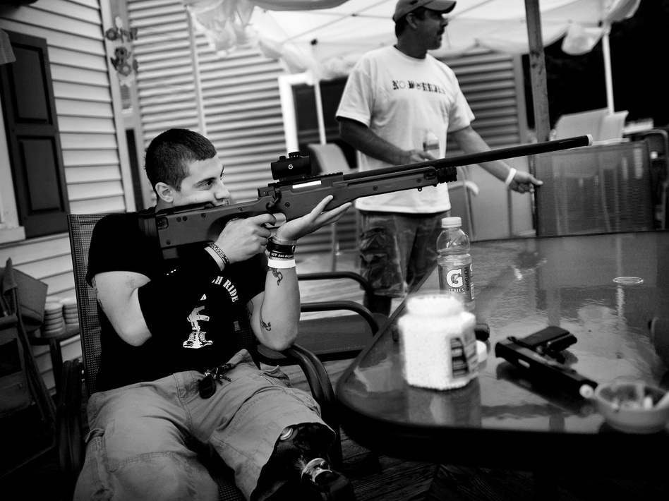 Staback takes aim with a replica sniper rifle on his back porch in Scranton, Pa. After a year at Walter Reed, he's moving into an apartment with a friend near the hospital in Bethesda, Md. (NPR)
