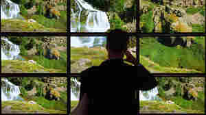A visitor looks at a bank of TV screens at a consumer electronics show in Berlin. While TV and movies are available on many devices, consumers often struggle to find exactly what they want, television critic Eric Deggans says.