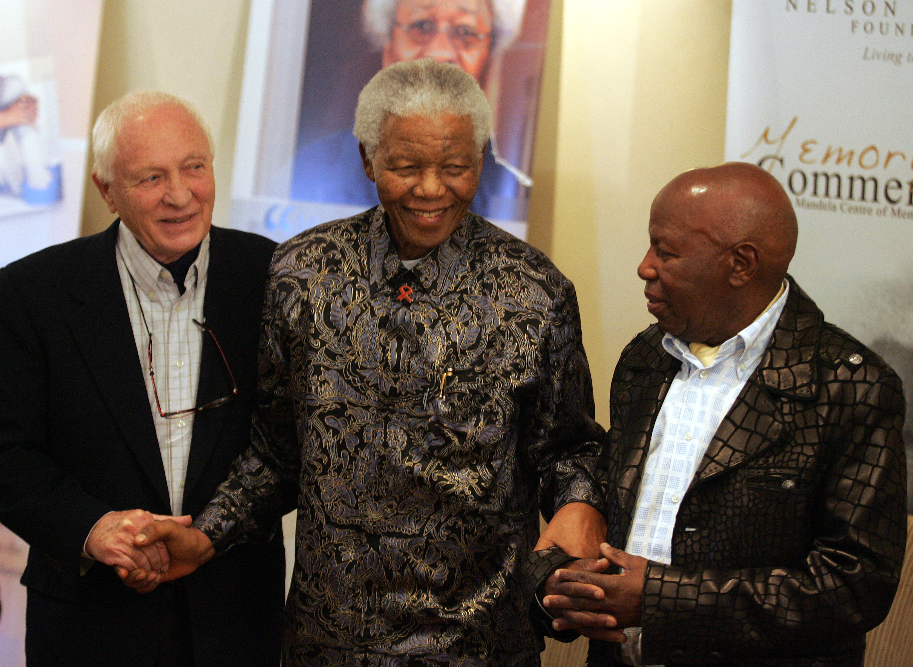 Kumalo stands with former South African President Nelson Mandela and photographer Jurgen Schadeberg during the launch of a photo exhibition at the Nelson Mandela Foundation in Johannesburg, July 12, 2006. Kumalo photographed Mandela and his family extensively throughout his career.