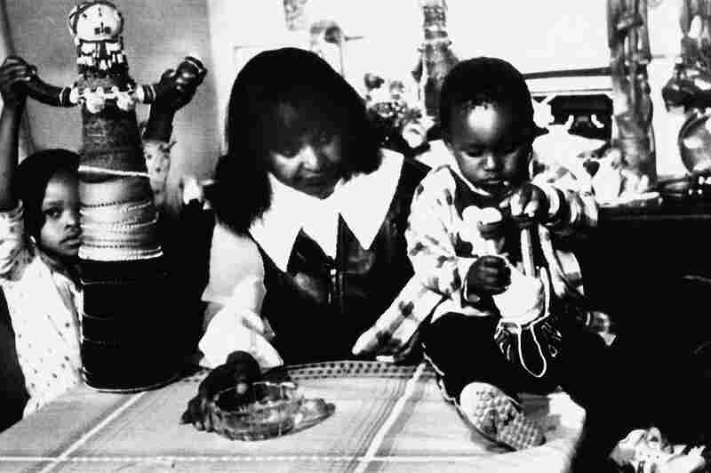 Winnie Mandela is seen with two of her grandchildren on Dec. 22, 1985, in Soweto, South Africa, after being forcibly removed from her home the day before. She was later arrested again the same day by South African police.