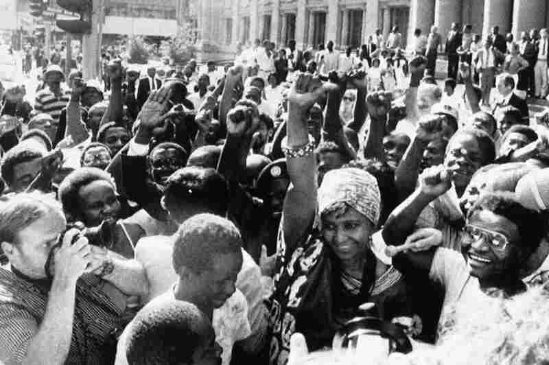 Winnie Mandela (wearing a turban) is mobbed by chanting supporters as she leaves the Supreme Court on Jan. 8, 1986, in Johannesburg, after she began a court suit seeking to overturn a government order banning her from her Soweto home.