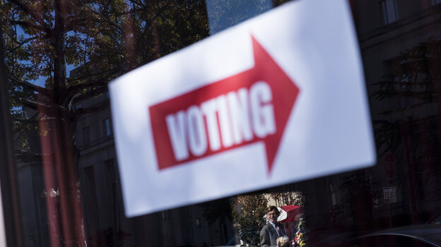 A sign directing voters to a polling place is seen during the first day of early voting on Monday in Washington, D.C.