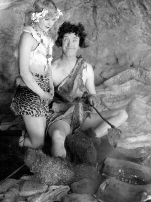 Actors Stan Laurel and Edna Marlon play at socializing around the campfire. It turns out that early man's bra