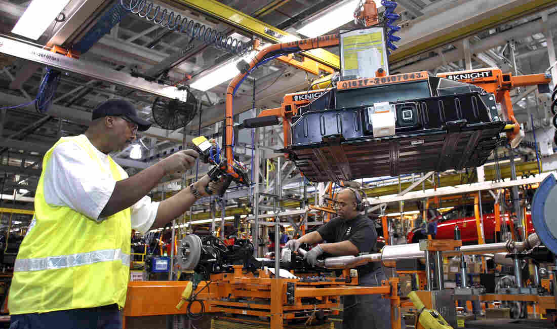 WAYNE, MI - DECEMBER 14: A worker demonstrates the installation of a battery pack for a Ford Focus on the assembly line at the Ford Motor Co.'s Michigan Assembly Plant December 14, 2011 in Wayne, Michigan.