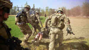 U.S. soldiers carry a comrade injured by an improvised explosive device, or IED, in Logar province, south of Kabul, on Oct. 13. Roadside bombs are