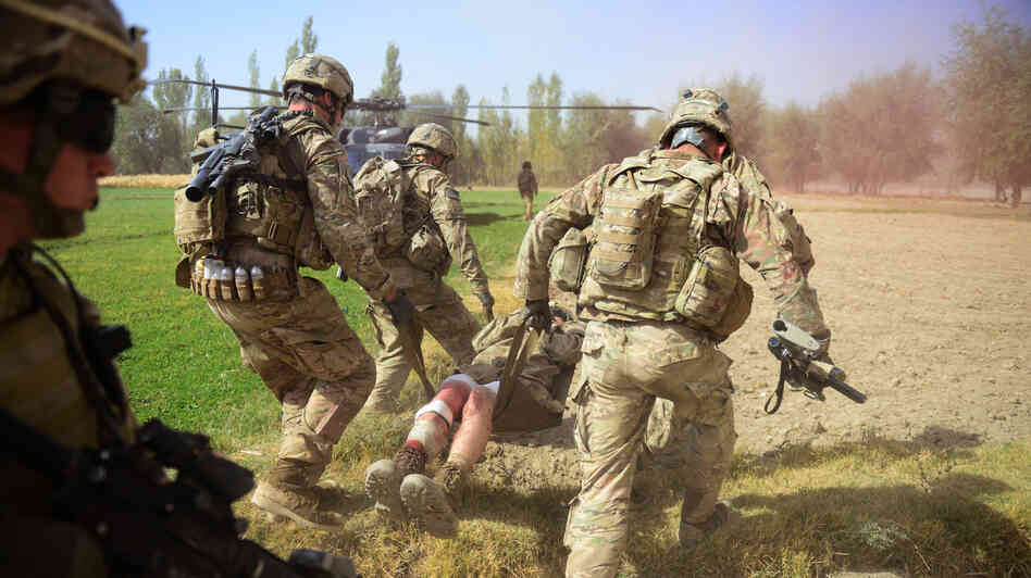 U.S. soldiers carry a comrade injured by an improvised explosive dev
