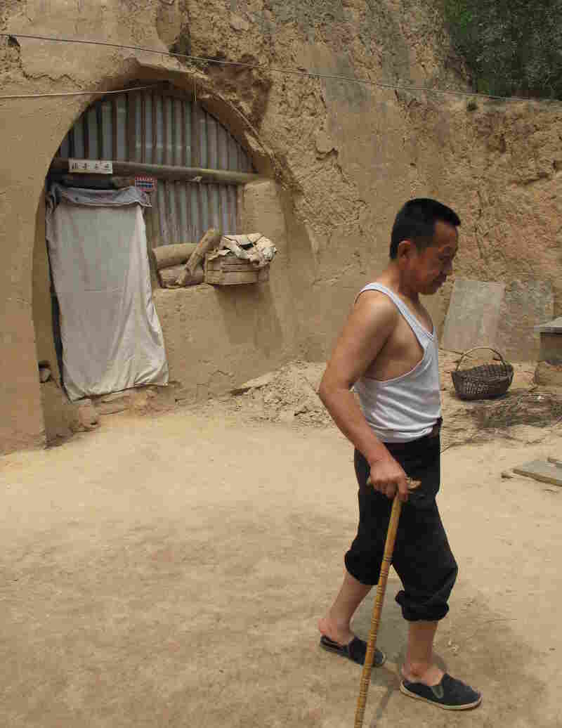 """Guo limps across the yard of his cave home, which has no running water. He says he is a big supporter of the Communist Party, but admits he envies city folk, who """"live and eat and do everything better than us"""" country folk."""