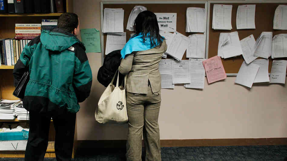 Two people check job listings at a New York State Department of Labor Emp