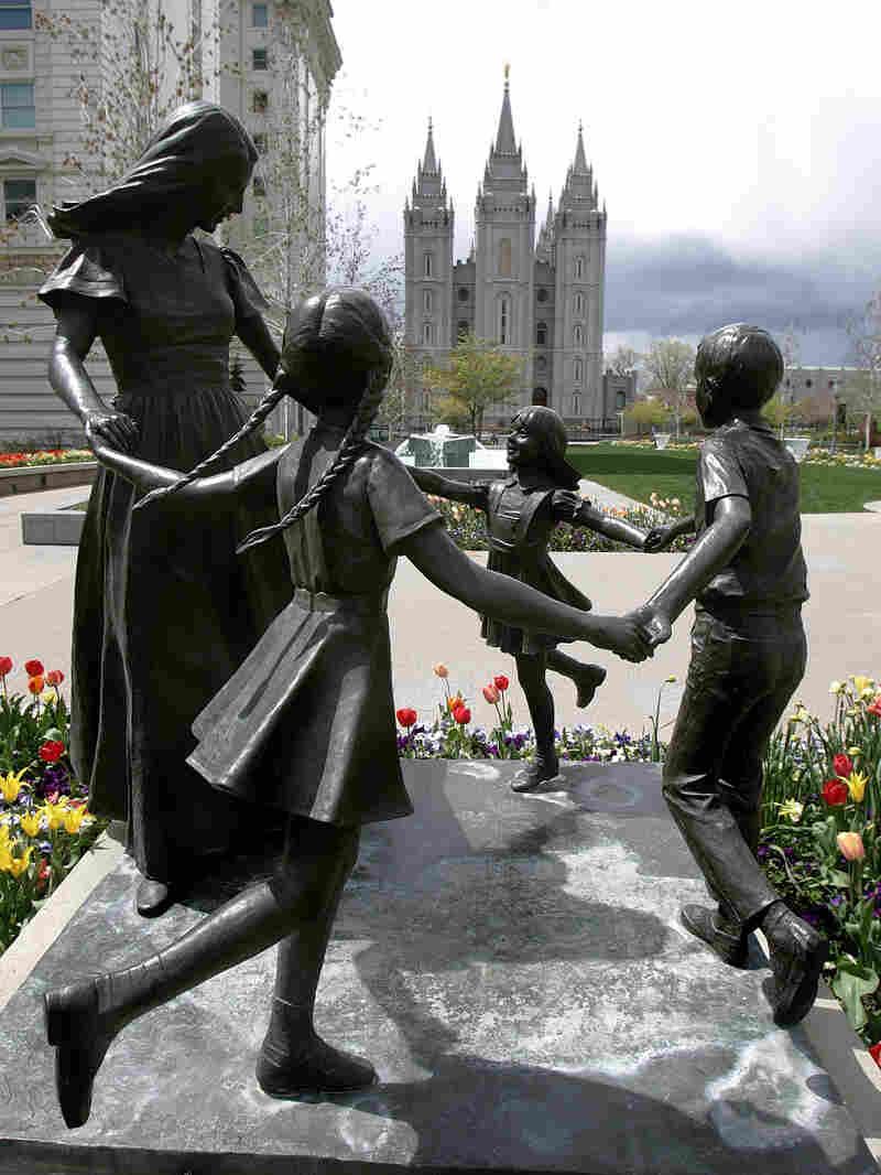 A statue representing womanhood — and women's role in raising children — is seen with the Mormon Temple in the background in Salt Lake City.