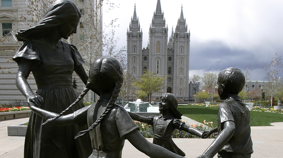 A statue representing womanhood — and women's role in raising children — is seen with the Mormon Temple in the background in Salt Lake City. (AP)