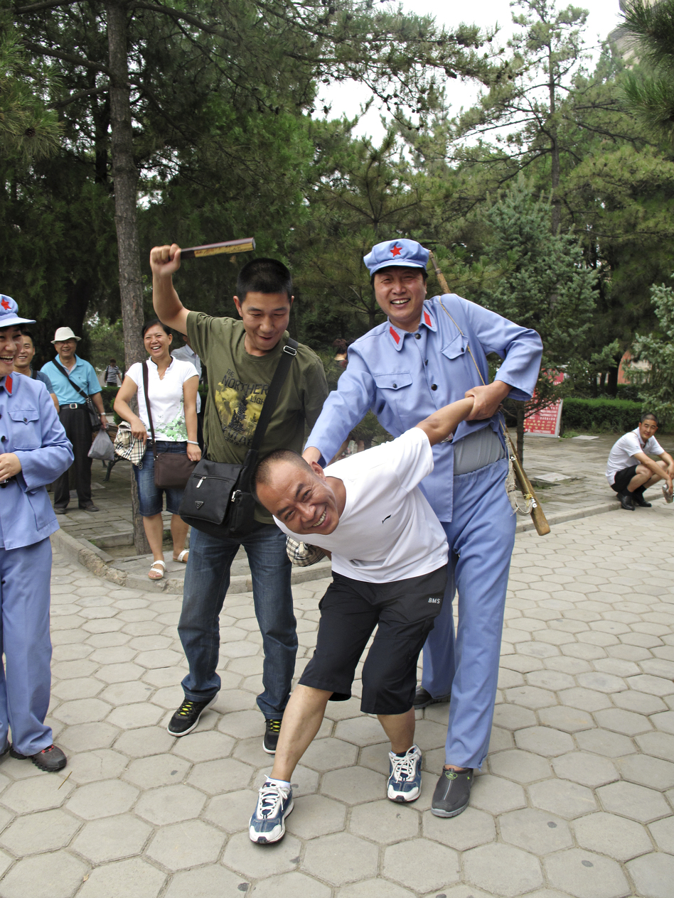"A tourist with a passing resemblance to Chairman Mao put another visitor in a stress position known as the ""airplane,"" which was often used on ""class enemies"" during the mass upheaval of China's Cultural Revolution, from 1966 to 1976. (NPR)"
