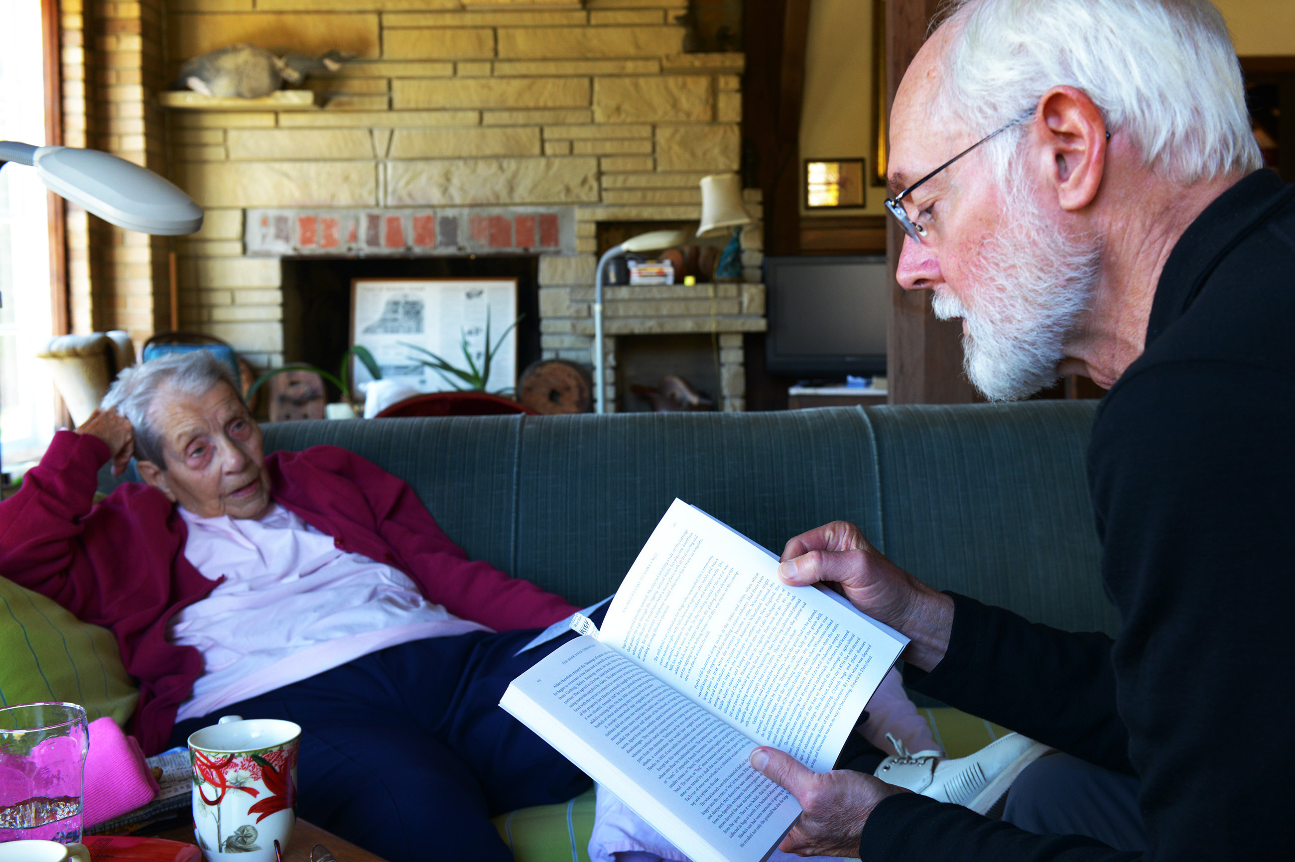 Margaret Zerwekh, who has lived in the mill house for half a century, listens to Milton Bates read from his book, Bark River Chronicles. Zerwekh's home is a treasure trove of Delafield history.