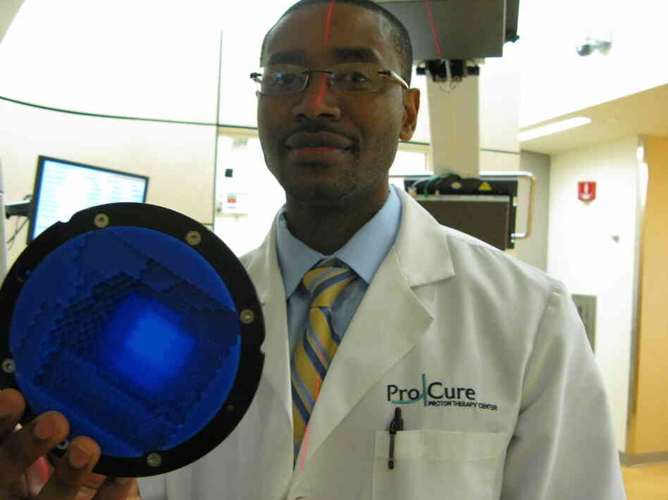 Radiation therapist Jean Etienne holds a range compensator, which shapes the depth to which the proton beam enters a patient's body to target a tumor.
