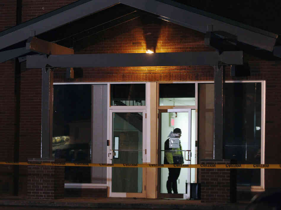 A Framingham police officer  keeps watch as federal agents search the New England Compounding Center company in Framingham, Mass., on October 16.