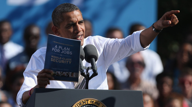 "President Obama holds a copy of ""The New Economic Patriotism: A Plan for Jobs & Middle-Class Security,"" which outlines some of his agenda for a second term, during a rally in Richmond, Va., on Thursday. (Getty Images)"